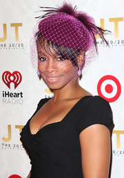 Anika Noni Rose added some color to her LBD with this decorative purple topper with feathers and netting.