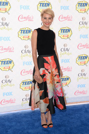 Chelsea Kane accessorized with an oval-shaped nude hard-case clutch.
