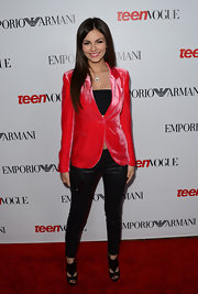 Victoria Justice paired cutout peep-toe pumps with her bright velvet blazer and black crop top.