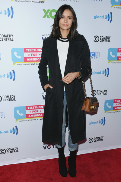 Nina Dobrev embraced the season in a black duster layered over a white sweater at the Telethon for America.