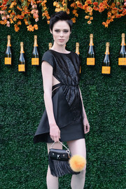 Coco Rocha arrived for the Veuve Clicquot Polo Classic carrying a fringed leather purse by Fendi.