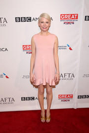 Michelle Williams styled her dress with gold knot sandals by Alumnae.