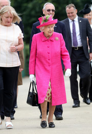Queen Elizabeth II cut a bright figure in a fuchsia embossed-silk coat by Angela Kelly while visiting the National Institute of Agricultural Botany.