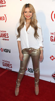DJ Havana Brown attended a party wearing a crisp white button-down top paired with gold skinny pants.