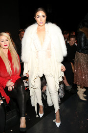 Underneath her fur cape, Olivia Culpo wore white skinny pants, a robe, and a sheer top, all exploding with ruffles!