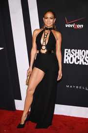 Jennifer Lopez burned up the Fashion Rocks red carpet in a black Atelier Versace gown featuring a leg-baring skirt and a navel-grazing neckline with metal embellishments.