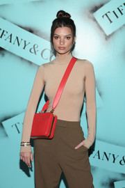 Emily Ratajkowski accessorized with a bright red Mark Cross bag for a pop of color to her neutral outfit at the Tiffany & Co. Modern Love photography exhibition.