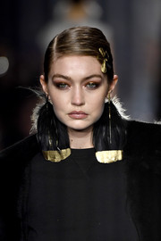 Gigi Hadid wore her hair in a side-parted updo while walking the Tom Ford Fall 2020 show.