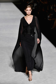 Gigi Hadid was diva-glam in a black column dress with a sheer cape and sleeves at the Tom Ford Spring 2019 show.