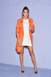 Sistine Stallone punched up a simple white dress with a stylish orange leather coat by Tom Ford for the label's Fall 2018 show.