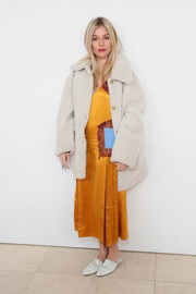 Sienna Miller chose a marigold Tory Burch slip dress with contrast pockets for the brand's Fall 2018 show.