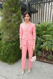A pale pink purse with a bedazzled buckle and a gold chain strap polished off Gemma Chan's ensemble.