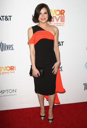 Lana Parrilla attended the 2016 TrevorLIVE LA wearing a black one-shoulder dress accented with red fabric across the yoke and down the back.