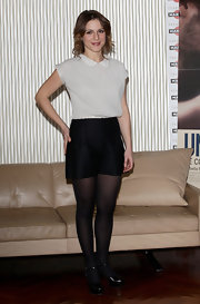 Isabella wears lovely silk black shorts with her white blouse and black tights.