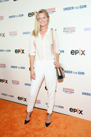 Toni Garrn teamed her shirt with a pair of white cigarette pants.