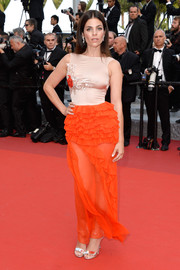 Julia Restoin-Roitfeld made an appearance at the Cannes premiere of 'The Unknown Girl' wearing a Christian Dior gown featuring a tight nude bodice and a bright-orange ruffle skirt.