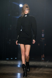 Gigi Hadid cut a strong silhouette in this bold-sleeved turtleneck dress while walking the Versus runway.