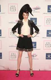 Coco Rocha went for a matador-inspired look in a beaded black skirt suit by Moschino during the VRC Oaks Club luncheon.