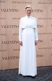 Tilda Swinton opted for an ultra-conservative long-sleeve white gown by Valentino for the label's fashion show.