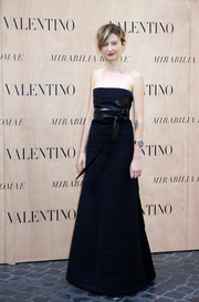 Alba Rohrwacher was all about edgy glamour at the Valentino fashion show in a black strapless gown accented with a crisscross leather belt.
