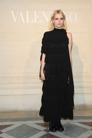 Lucy Boynton completed her look with a black leather clutch by Valentino.