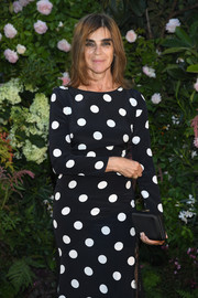 Carine Roitfeld paired a black satin clutch with a polka-dot dress for the Valentino Couture Fall 2018 show.