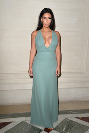Kim Kardashian gave us an eyeful of cleavage and curves in a plunging blue-gray Valentino gown during the label's fashion show.