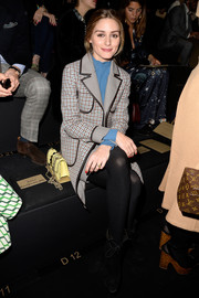 Olivia Palermo attended the Valentino fashion show wearing a leather-trimmed, checkered coat.