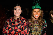 Anna dello Russo looked quirky with her green feathered Prada headband at the Valentino fashion show.