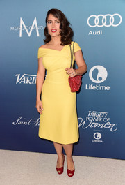Going for a striking color combo, Salma Hayek paired her yellow frock with a red woven-leather bag by Bottega Veneta.