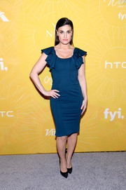 Idina Menzel went for a feminine vibe in a figure-hugging blue ruffle-sleeve dress by Zac Posen at the Variety Power of Women event.