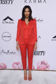 Padma Lakshmi matched her suit with a pair of red crisscross-strap sandals.