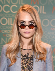 Cara Delevingne accessorized with a pair of round sunnies for a fun touch to her look.