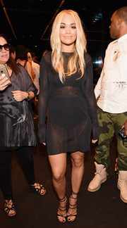 Rita Ora flashed some skin in a sheer black sweater dress by Vera Wang during the label's fashion show.