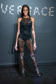 Winnie Harlow worked a barely-there black gown by Versace during the brand's Pre-Fall 2019 show.