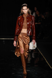 Kaia Gerber looked fierce in a brown patent jacket layered over a cropped sweater at the Versace runway show.