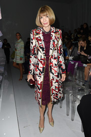 Anna Wintour looked flawless in a geometric-print coat layered over a burgundy lace dress at the Versace fashion show.