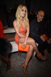 Rita Ora showed off an orange Versace Medusa clutch while attending the brand's Haute Couture fashion show.