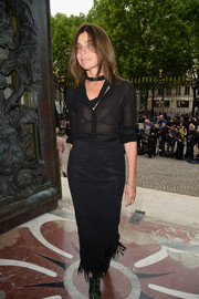 Carine Roitfeld stuck to her trademark style with this fringed black pencil skirt and blouse combo at the Versace Haute Couture fashion show.