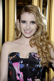 Emma Roberts wore her long golden locks in cascading curls at the Versace for H&M fashion event.