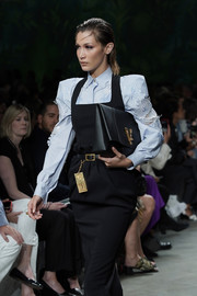 Bella Hadid carried an oversized black leather clutch while walking the Versace Spring 2020 runway.