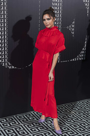 Victoria Beckham went for a demure red ruffle-neck midi dress from her own label when she attended the Vogue dinner in Madrid.