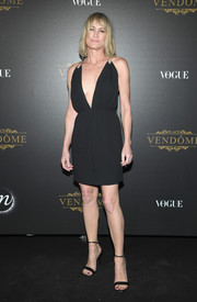 Robin Wright paraded her fab figure in a Saint Laurent LBD with a navel-grazing neckline at the Vogue party in Paris.