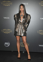 Naomi Campbell put on a leggy display in a gold mini dress by Saint Laurent at the Vogue party in Paris.