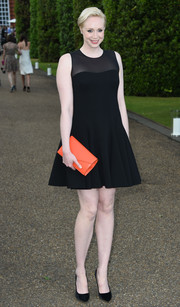 Gwendoline Christie added a bright pop with an orange envelope clutch, also by Ralph Lauren.
