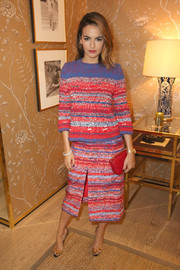 Camilla Belle styled her look with a red Tory Burch Kira clutch.