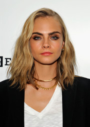 Cara Delevingne topped off her ensemble with a pair of gold necklaces.