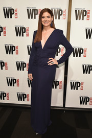Debra Messing attended the WP Theater Gala wearing a navy Michael Kors gown with a deep-V plunge and a ruched midsection.
