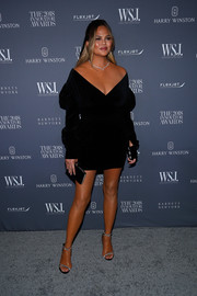 Chrissy Teigen completed her ensemble with a black velvet clutch by Judith Leiber.