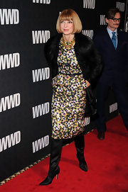 Anna Wintour chose black satin knee-high boots to wear with a belted floral shift dress.